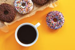 Delicious glazed donuts and cup of coffee on yellow surface royalty free stock photography