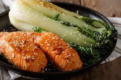 Delicious glazed salmon fillet with sesame and bok choy close-up Royalty Free Stock Image