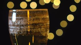 Delicious golden beer in a glass is spinning on background of blurred lights. stock video footage