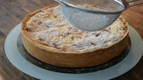 A delicious gooseberry cake with crumble is sugared on a turntable with icing sugar stock video footage
