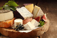 Delicious gourmet cheese platter. With a wide assortment of soft and semi-hard cheeses served with sliced sweet fresh figs and grapes on a rustic wooden table Stock Image