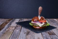 Delicious gourmet cheeseburger with knife Royalty Free Stock Photos