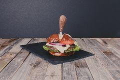 Delicious gourmet cheeseburger with knife Royalty Free Stock Photo