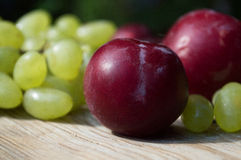 Delicious grapes and fruits on a table. Delicious grapes and fruits on a wooden table Royalty Free Stock Photo