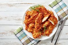Delicious grated potato coated and deep fried pork chops on a plate on a rustic white wooden table with napkin, fork and knife,. View from above, flatlay stock image