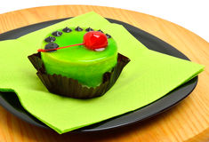 Delicious green cake with cherry on black plate on cutting backg Stock Images