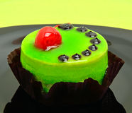 Delicious green cake with cherry on black plate on green backgro Stock Images