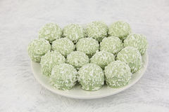 Delicious green coconut candies on white plate on  white backgro Royalty Free Stock Images