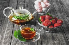 Delicious green mint strawberry tea in a transparent glass teapot and Cup in the summer, on a rustic wooden table with strawberrie Stock Image