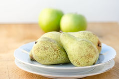 Delicious green pears on white plate with apples on background Royalty Free Stock Photos