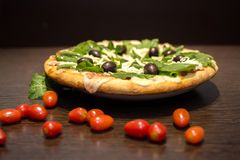 Delicious green pizza and tomatoes stock image