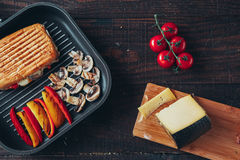 A delicious griled panini sandwich with mushrooms, cheese, pepper and tomato.  Stock Image