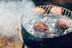 Delicious grilled beef meat laying on barbecue with fire and smoke in forest. picnic grill vacation. Rest Stock Image