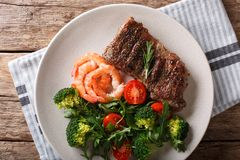 Delicious grilled beef steak with prawns and broccoli, tomatoes, arugula closeup on a plate. Surf and Turf. horizontal top view stock images