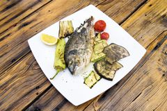 Delicious Grilled  bream or dorade fish on wooden background Royalty Free Stock Photos