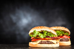 Delicious grilled burger. On black background Royalty Free Stock Images
