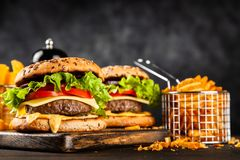 Delicious grilled burgers. Delicious grilled hamburgers on dark background stock images