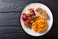 Delicious grilled chicken with garnish of sweet potato and fresh. Salad close-up on a plate on the table. horizontal top view from above stock images