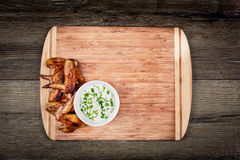Delicious grilled chicken wings with garlic sauce on a cutting board on wooden rustic background with copyspace top view Royalty Free Stock Photo