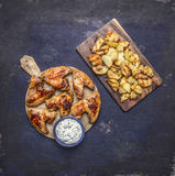 Delicious grilled chicken wings garlic sauce and fried potatoes with dill on wooden rustic background top view close up Stock Photo