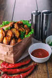 Delicious grilled chicken wings with garlic and tomato sauce with lettuce in food paper bag on wooden rustic background Stock Images