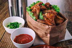 Delicious grilled chicken wings with garlic and tomato sauce with lettuce in food paper bag on wooden rustic background Stock Photos