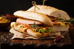 Delicious grilled hot dog with sausage and bacon, ketchup and mu. Stard on a wooden background stock photo