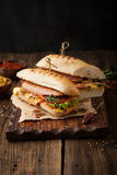 Delicious grilled hot dog with sausage and bacon, ketchup and mu. Stard on a wooden background royalty free stock photo