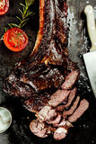Delicious grilled lean tomahawk beef steak. Cut through to reveal the tender meat on a griddle with fresh rosemary and tomato, overhead view stock photos