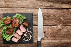 Delicious grilled meat. Kebab served on wood Stock Photography