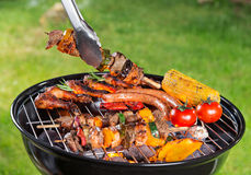 Delicious grilled meat with vegetable on a barbecue grill. Assorted delicious grilled meat with vegetable on a barbecue grill Royalty Free Stock Photography