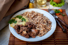 Delicious grilled meat with vegetable and buckwheat. Hot gulyash, roast meat, in white souce Stock Photos