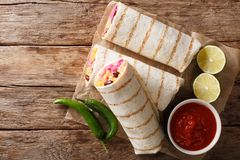 Delicious grilled mexican vegan burrito with rice, beans, corn,. Tomatoes, peppers and cabbage close-up on the table. Horizontal top view from above royalty free stock photography