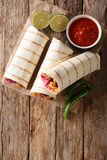 Delicious grilled mexican vegan burrito with rice, beans, corn,. Tomatoes, peppers and cabbage close-up on the table. Vertical top view from above stock image