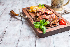 Delicious Grilled Pork Rib. And Fried Potato Wedges with Sauce on wooden cutting board, white wooden background stock images