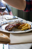 Delicious grilled pork ribs with barbecue sauce. Over old ceramic plate, in the restaurant Royalty Free Stock Photo