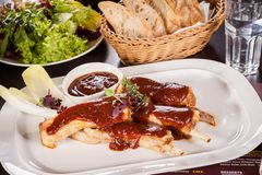 Delicious grilled pork ribs. Served with a rich brown gravy or BBQ sauce garnished with fresh herbs , close up side view Stock Photo