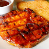 Delicious grilled pork steak and crispy fish fillet Stock Photos