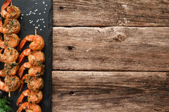 Delicious grilled prawns on black slate, top view. Japanese seafood. Fried spicy shrimps with herbs on wooden skewers served on black slate, flat lay. Rustic Stock Image