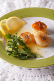Delicious grilled scallops with sauce and lemon on a plate.  Ver Stock Images