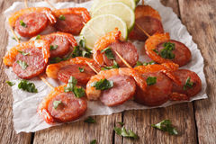 Delicious grilled shrimp with chorizo on skewers and herbs close Stock Photography