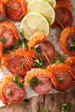 Delicious grilled shrimp with chorizo on skewers and herbs close Royalty Free Stock Photos