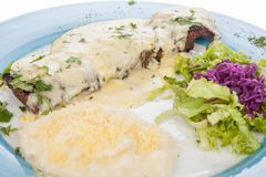 Delicious grilled steak topped with cheese sauce served with salad and potato puree. On white background Stock Image
