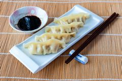 Delicious gyoza or pot stickers on bamboo mat. Gyoza or potstickers on a plate over a bamboo mat, with chopsticks and dipping sauce. Selective focus and royalty free stock photo