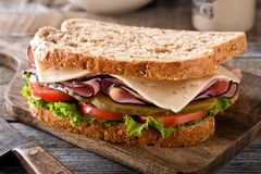 Ham and Cheese Sandwich. A delicious ham and cheese sandwich with lettuce, tomato and dill pickle on a rustic wood table royalty free stock image