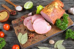 Delicious ham on cutting board, close-up. Delicious ham cut in slices with spices, parsley and lime on dark wooden cutting board on old wooden table. mustard Royalty Free Stock Photography