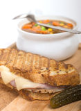 Delicious ham, pork and swiss cheese panini with vegetable soup. Delicious panini made with ham, pork and swiss cheese served with a vegetable soup, and pickles Stock Photography