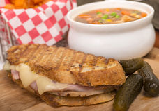 Delicious ham, pork and swiss cheese panini with vegetable soup. Delicious panini made with ham, pork and swiss cheese served with a vegetable soup, sweet potato Royalty Free Stock Image