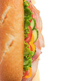 Delicious ham & turkey sandwich - top shot. Top view of a fresh submarine sandwich with lettuce, cheese, turkey, ham, yellow peppers, cucumbers and tomatoes Stock Photography