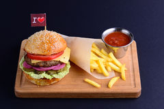 Delicious hamburger with beef, onion, lettuce, tomato served with potato fries and ketchup on wooden board. Burger menu on a black background with a copy space Royalty Free Stock Photo
